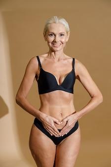 Photo de studio d'une femme blonde mature souriante en sous-vêtements noirs tenant la main sur son ventre formant un