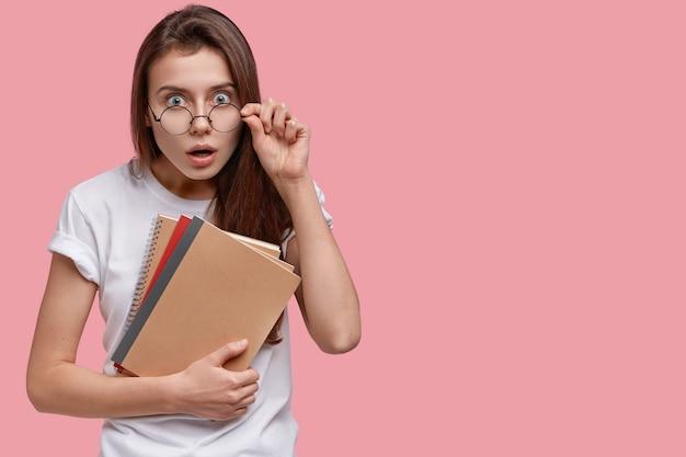 Photo de studio de femme brune choquée garde la main sur le bord de lunettes, habillée en t-shirt décontracté