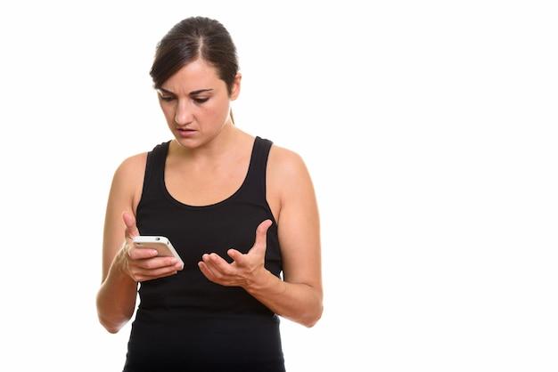 Photo de studio de femme en colère tenant un téléphone mobile