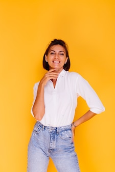Photo de studio de femme heureuse cheveux courts portant chemise blanche et pantalon en denim posant sur mur jaune