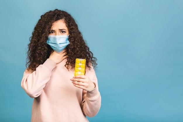 Photo de studio de femme infectée avec des pilules dans les mains, dame portant un masque protecteur