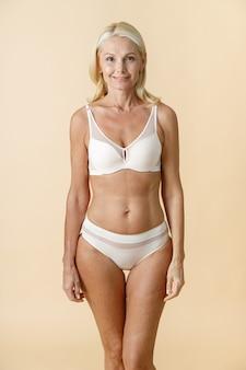 Photo de studio d'une femme mûre confiante aux cheveux blonds en sous-vêtements blancs posant pour la caméra