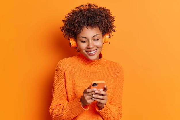 Photo de studio d'une femme à la peau assez sombre choisit la chanson de la liste de lecture utilise un smartphone et un casque sans fil