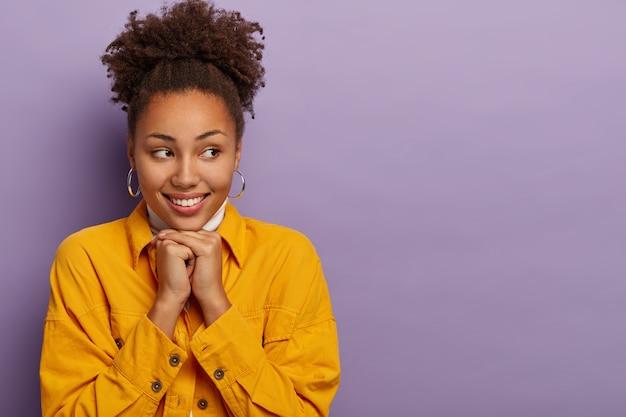 Photo de studio d'une femme à la peau foncée avec des cheveux bouclés, porte des boucles d'oreilles et une veste en jean jaune, garde les mains sous le menton, regarde de côté, exprime des émotions sincères, sourit insouciant, copiez l'espace de côté