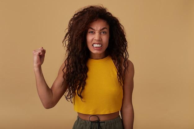 Photo de studio de femme à la peau foncée longue et bouclée irritée grimaçant son visage tout en regardant avec colère la caméra, gardant sa main levée en se tenant debout sur fond beige