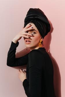 Photo de studio de femme sensuelle porte des boucles d'oreilles dorées