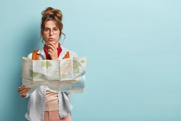 Photo de studio de femme touriste réfléchie sérieuse tient le menton, planifie son voyage, détient une carte papier