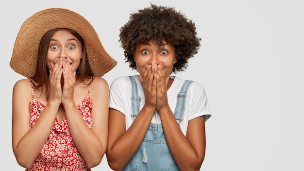 Photo de studio de femmes métisses surpris et ravies de joie couvrent la bouche avec des paumes