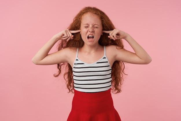 Photo de studio de fille bouclée aux cheveux longs rousse debout sur fond rose avec les yeux fermés, insérant l'index dans ses oreilles pour éviter les sons forts, portant des vêtements de fête