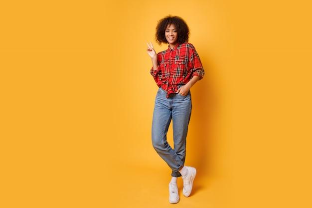 Photo de studio de fille noire sautant avec une expression de visage heureux sur fond orange vif. portant un jean, des baskets blanches et une chemise rouge.