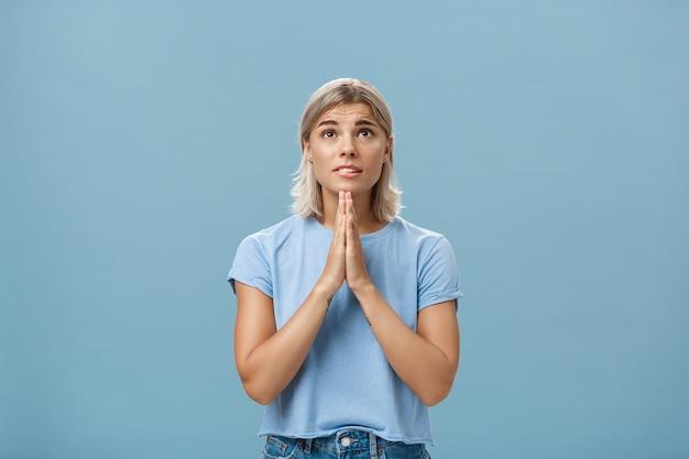 Photo de studio de fille rêveuse focalisée pleine d'espoir avec un visage attrayant et des cheveux blonds tenant par la main en priant près du corps en levant avec espoir avec foi priant ou souhaitant sur le mur bleu