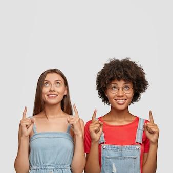 Photo de studio d'heureuses jeunes femmes métisses vêtues de vêtements à la mode, montrer l'espace libre au-dessus