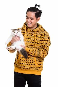 Photo de studio d'heureux homme asiatique souriant tout en tenant un chat mignon