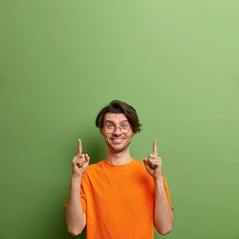 Photo de studio d'heureux homme européen mal rasé avec une expression positive pointe vers le haut sur un espace vide