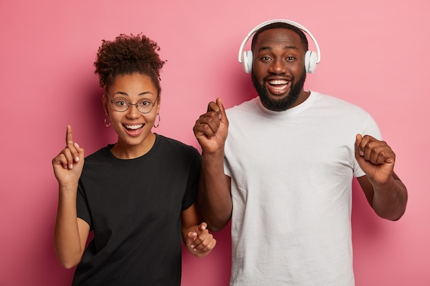 Photo de studio d'heureux homme et femme noire dansant au rythme de la musique