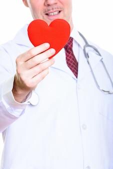 Photo de studio d'heureux homme mûr médecin souriant tout en tenant coeur rouge