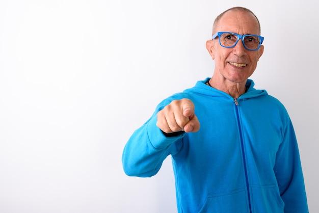 Photo de studio d'heureux homme senior chauve souriant et pointant la caméra