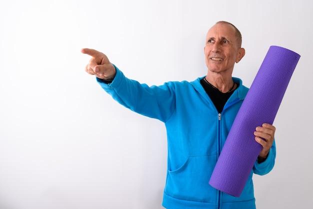 Photo de studio d'heureux homme senior chauve souriant tout en tenant un tapis de yoga