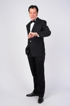 Photo de studio d'homme d'affaires beau mature portant smoking contre blanc