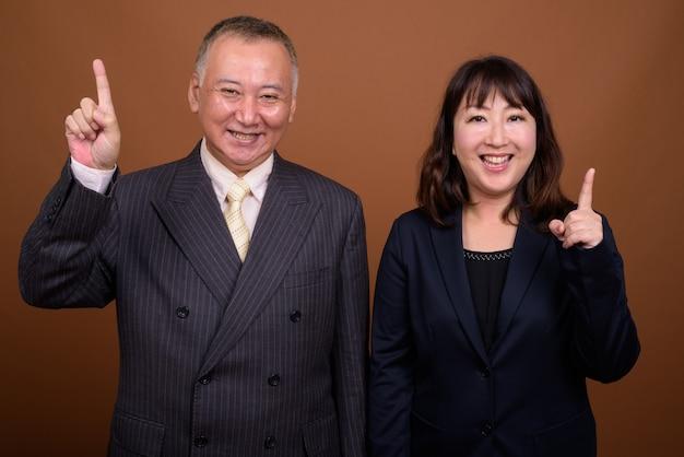 Photo de studio d'homme d'affaires japonais mature et femme d'affaires japonaise mature ensemble sur fond marron