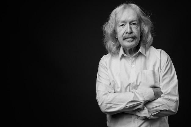 Photo de studio d'un homme d'affaires senior avec une moustache portant une chemise rose contre un mur gris