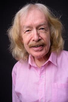 Photo de studio d'homme d'affaires senior avec moustache portant une chemise rose sur fond gris