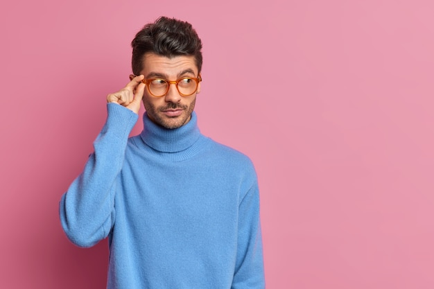Photo de studio d'un homme européen réfléchi concentré pensivement de côté