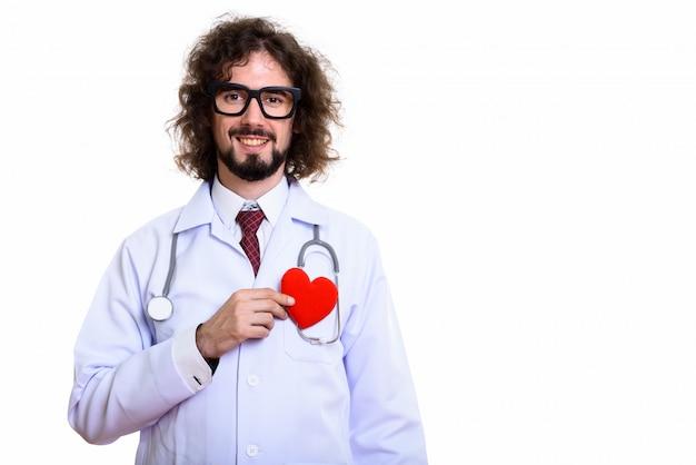 Photo de studio d'homme heureux médecin souriant tenant coeur rouge contre