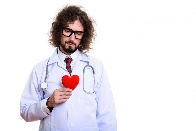 Photo de studio d'homme médecin tenant un coeur rouge à la triste