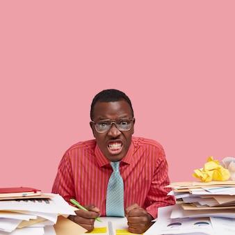 Photo de studio d'un homme à la peau foncée irritée serre les dents, garde les mains dans les poings, vêtu de vêtements formels