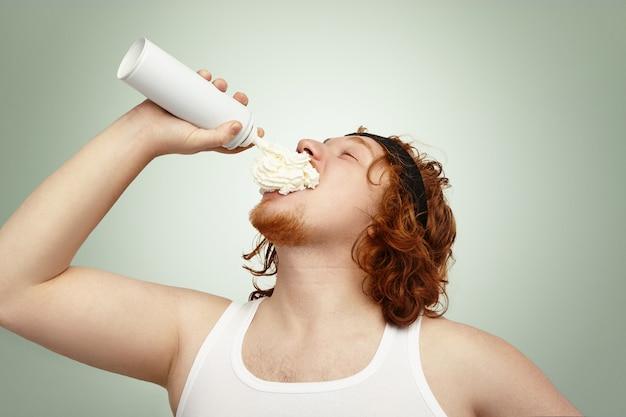 Photo de studio d'un homme de race blanche en surpoids obèse avec des cheveux bouclés au gingembre, pulvérisation de crème fouettée dans sa bouche