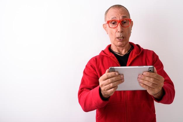 Photo de studio d'homme senior chauve à l'aide de tablette numérique