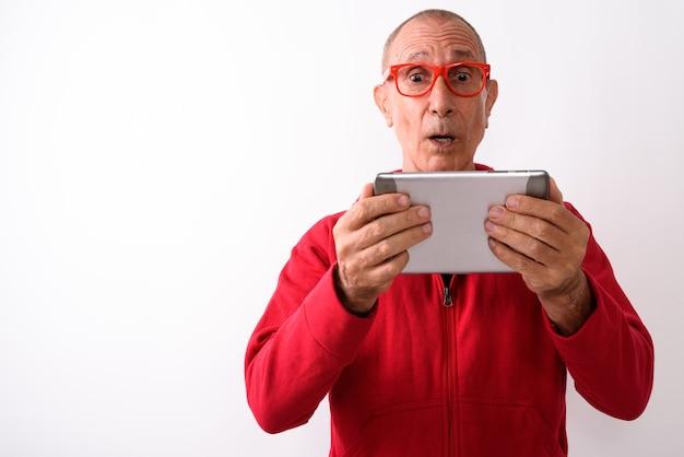 Photo de studio d'homme senior chauve choqué à l'aide de tablette numérique