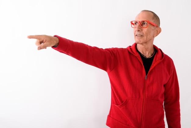 Photo de studio d'homme senior chauve pointant à distance tout en portant des lunettes