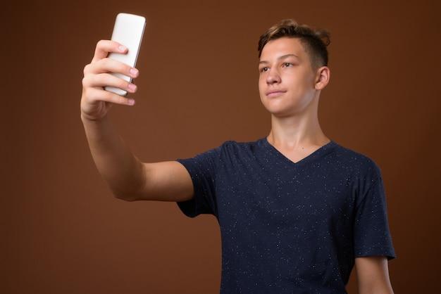 Photo de studio de jeune adolescent beau contre backgrou brun