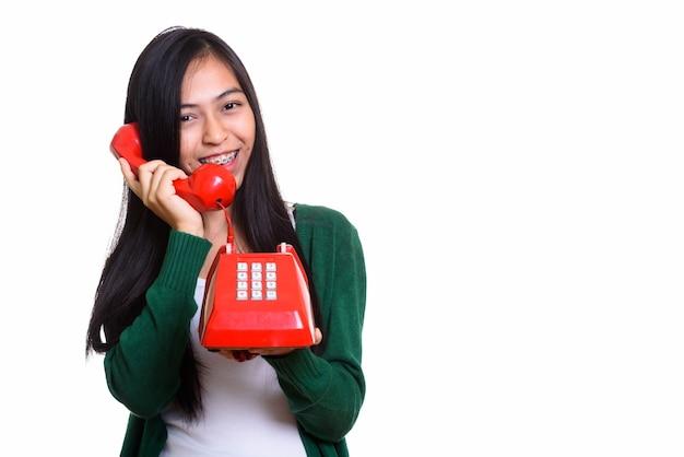 Photo de studio de jeune adolescente asiatique heureuse souriant