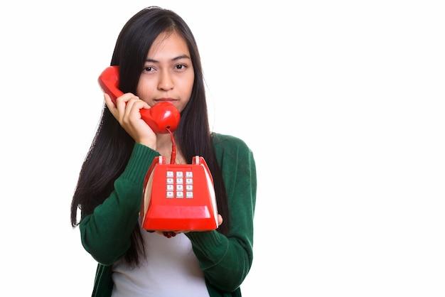 Photo de studio de jeune adolescente asiatique parlant sur le vieux téléphone