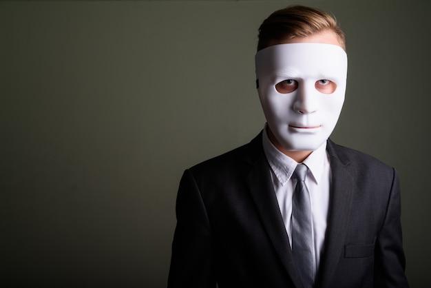 Photo de studio de jeune bel homme d'affaires portant costume sur fond coloré