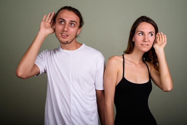 Photo de studio de jeune bel homme et belle jeune femme ensemble sur fond coloré