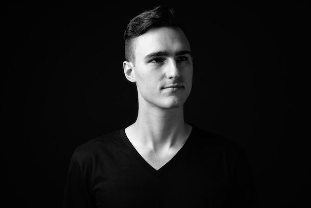 Photo de studio de jeune bel homme sur fond noir en noir et blanc
