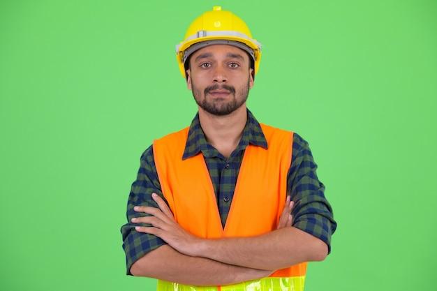 Photo de studio de jeune bel homme persan barbu travailleur de la construction contre chroma key avec fond vert