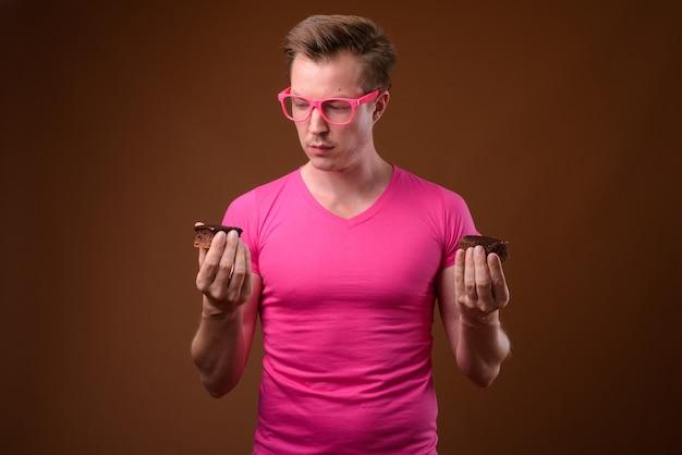 Photo de studio de jeune bel homme portant une chemise rose avec des lunettes roses assorties tout en ayant un gâteau au chocolat sur fond marron