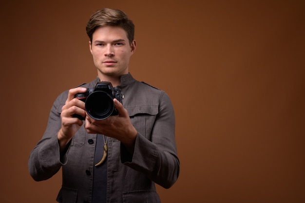 Photo de studio de jeune bel homme en tant que photographe avec appareil photo