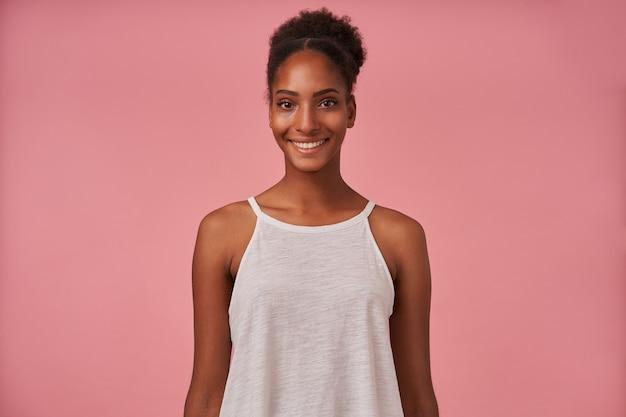 Photo de studio de jeune belle dame frisée aux cheveux bruns avec regardant à l'avant avec un sourire charmant et en gardant les mains baissées tout en posant sur un mur rose