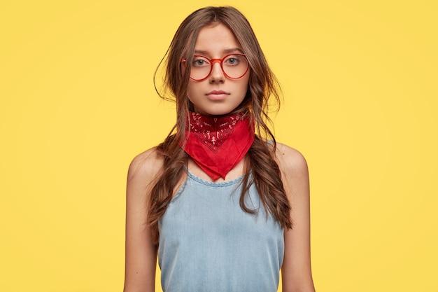 Photo de studio de jeune brune sérieuse avec des lunettes posant contre le mur jaune