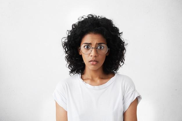 Photo de studio de jeune femme aux yeux de bogue effrayée se sentant effrayée et choquée