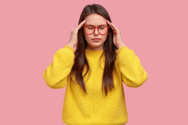 Photo de studio de jeune femme brune concentrée frotte les tempes, a mal à la tête, se sent surmenée