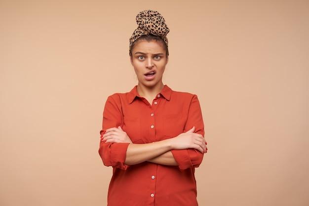 Photo de studio de jeune femme brune perplexe avec bandeau grimaçant confusément son visage tout en regardant à l'avant et les mains sur la poitrine, isolé sur un mur beige