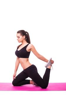 Photo de studio d'une jeune femme en forme faisant des exercices de yoga isolé sur fond blanc