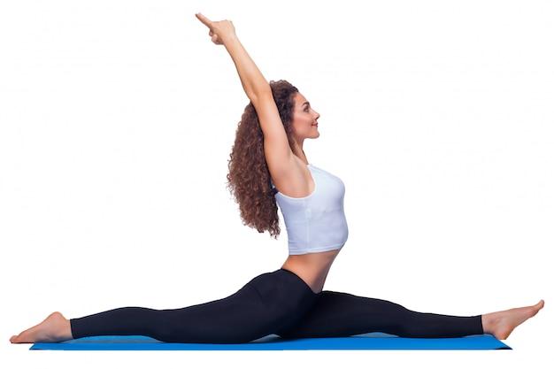 Photo de studio d'une jeune femme en forme faisant des exercices de yoga.